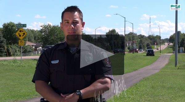 Screenshot of play button on police officer video
