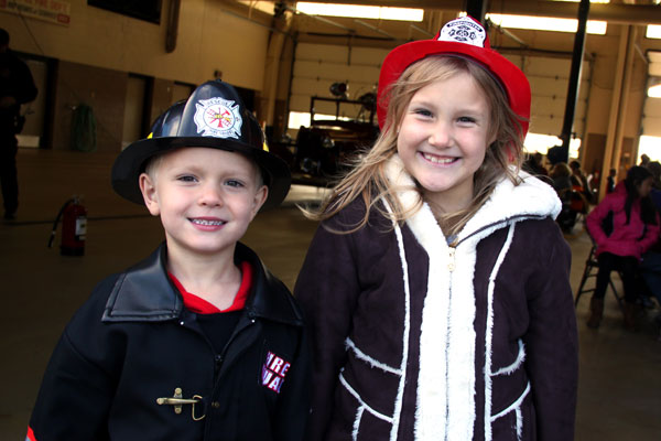 Brother and sister wearing firefighter hats