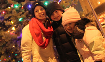 Kids smiling in front of Christmas Tree