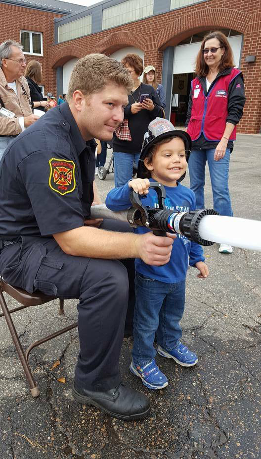 Little boy with firefighter and fire house