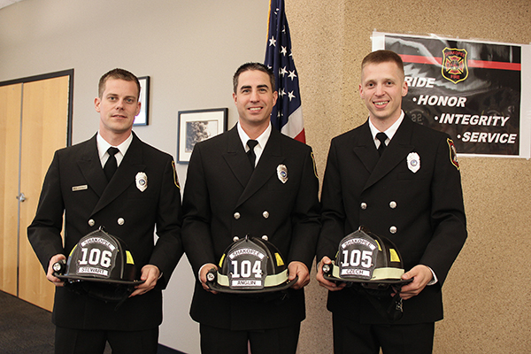 New firefighters hold helmets