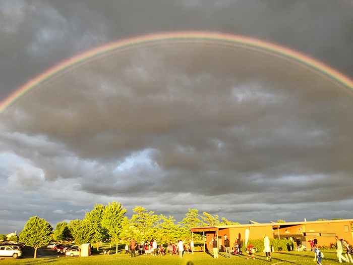 People gathered at 17th Avenue Sports Complex under rainbow