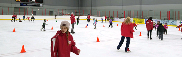 Instructors teaching kids how to ice skate