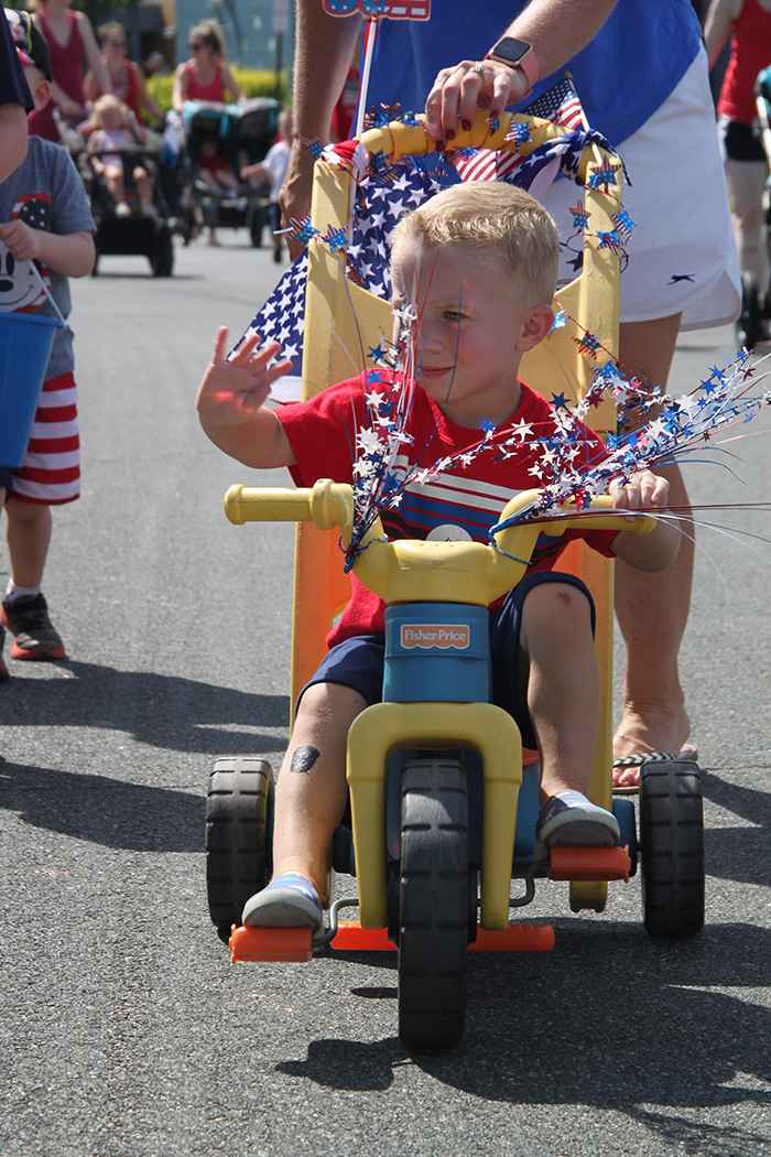 Boy waves from parade route
