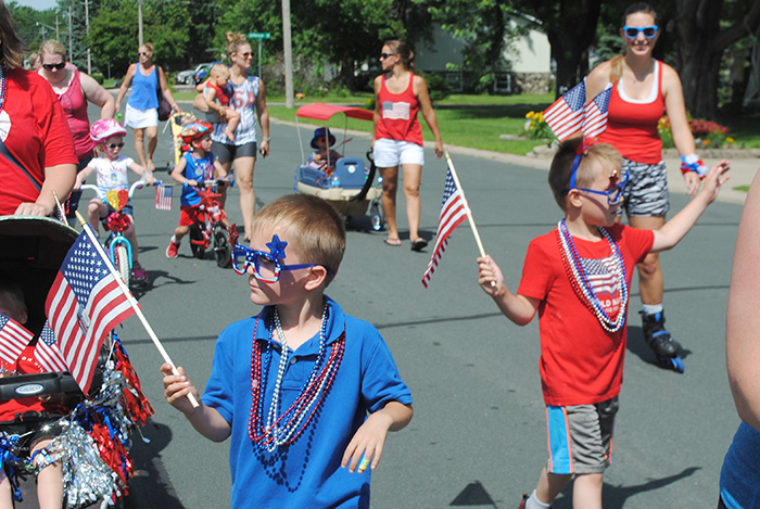 Kids waving while walking in parade
