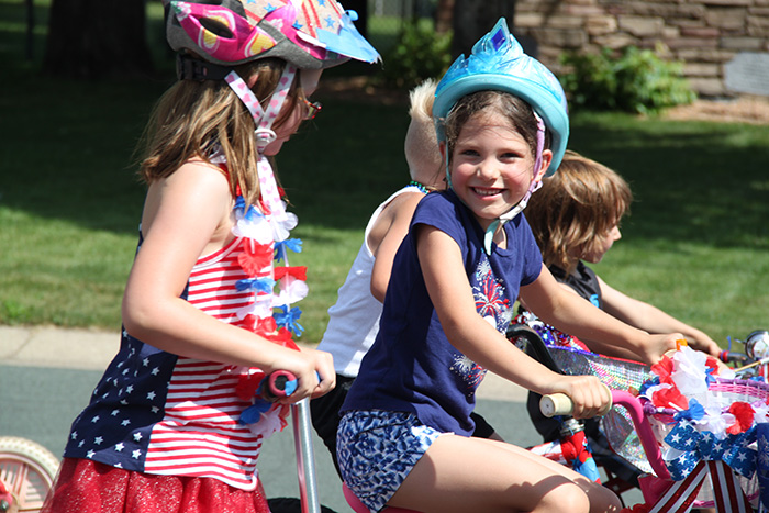 Girls riding bike in parade