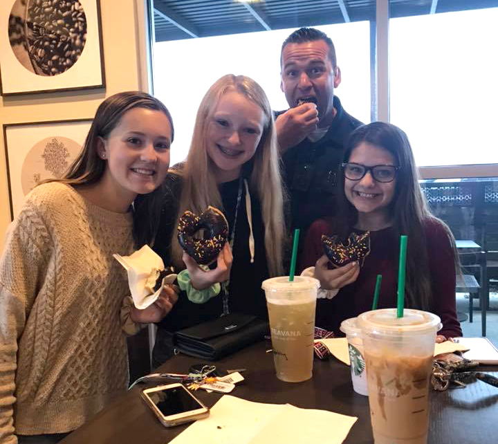 Officer eating donut with three smiling female teenagers