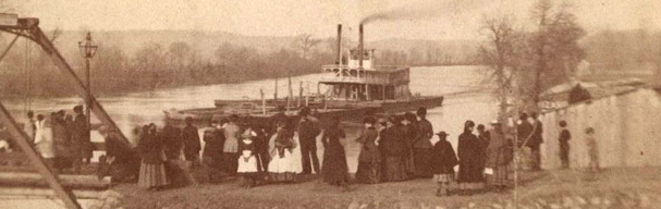People gathered by bridge with steamboat