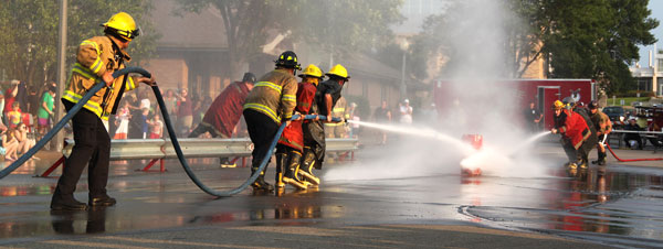 Firefighters spraying barrel with hose