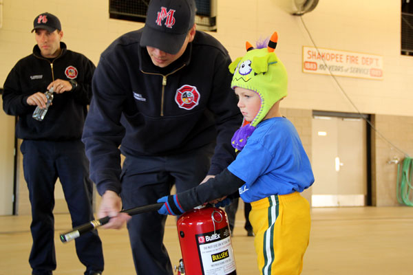 Firefighter helping boy with fire extinguisher