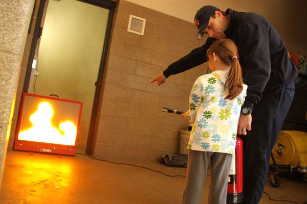 Firefighter helping girl with fire extinguisher