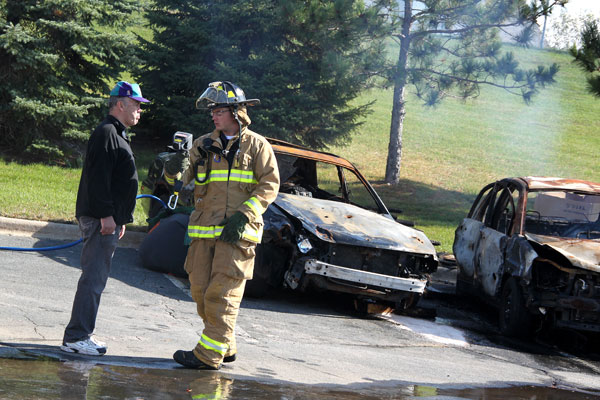 Firefighter in fire gear talking in front of burned-out cars