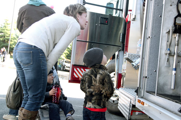 Mom and two kids looking at equipment on fire truck