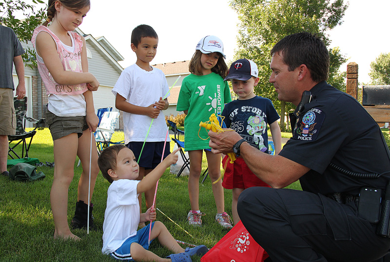 Officer hands out toys with kids on Cardinal Drive.