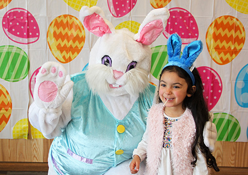 Easter Bunny poses for photo with girl in bunny ears
