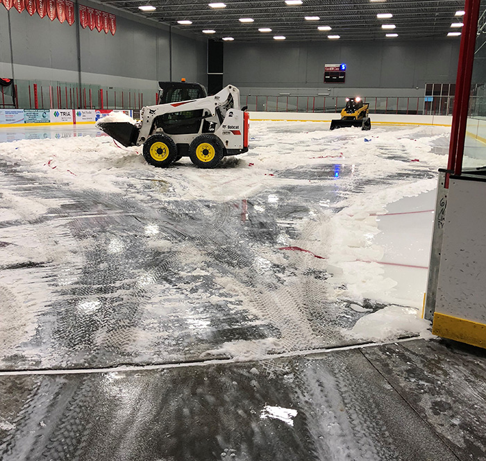 Crews use skidloaders to remove melting ice from ice arena floor