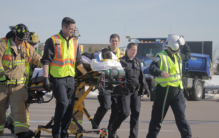 Responders walk injured patient on stretcher to helicopter