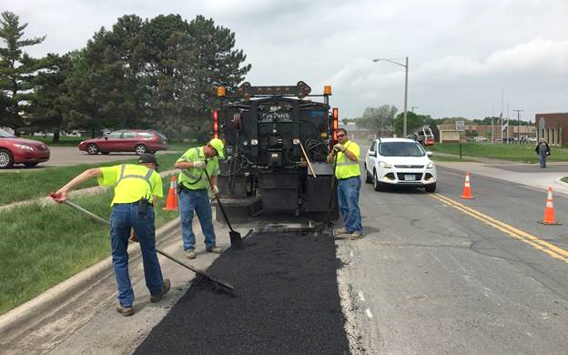 Crews adding new bituminous to fill pothole