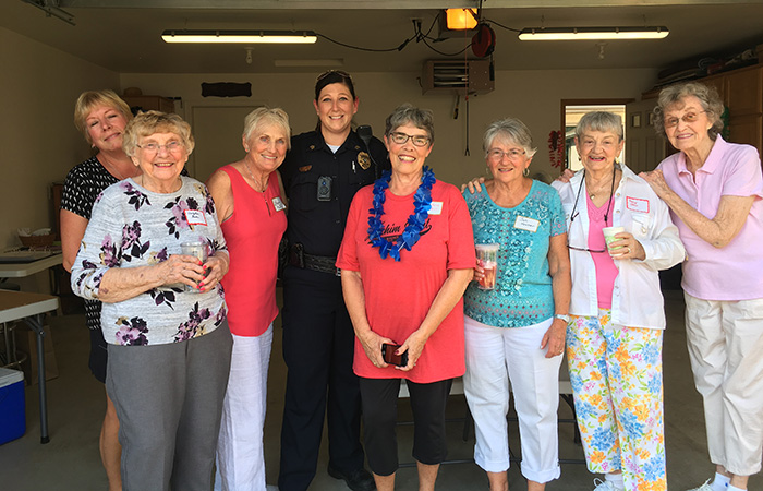 Police officer poses with seven women