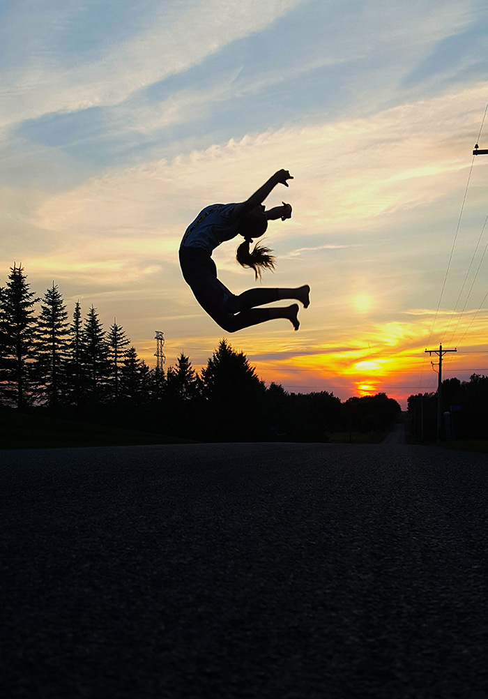 Girl leaping in front of sunse