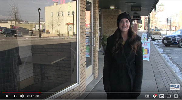 Woman wearing hat standing on street and talking to camera