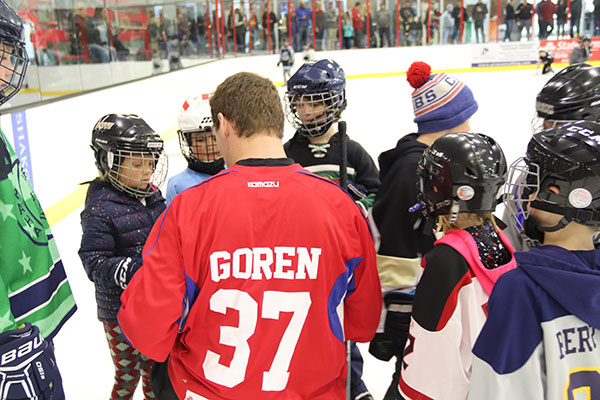 Former NHL hockey player Lee Goren signs autographs for kids