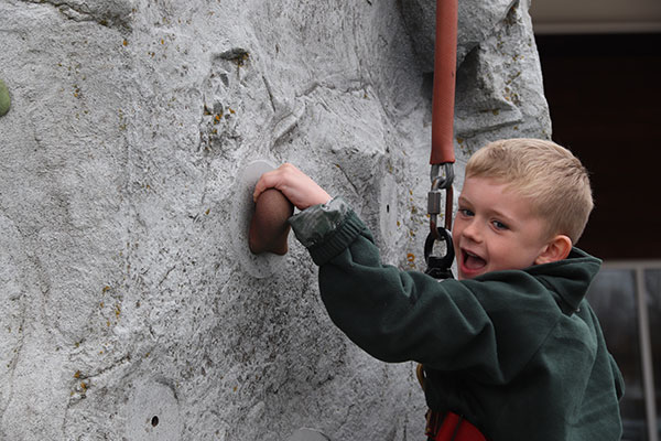 Boy climbs wall outside the ice arena