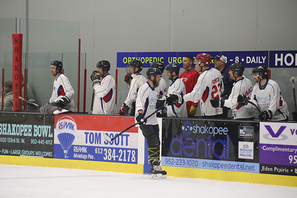 Youth hockey coaches congratulate on bench