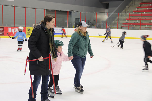 Two women skate with little girl