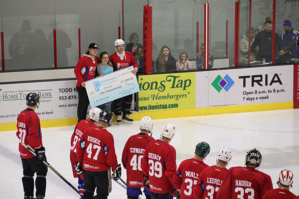 Current NHL Player Brock Boeser awards the Parkinson's Foundation with $1,000 check