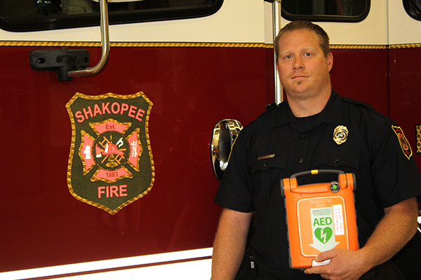 Firefighter holds AED in front of a fire truck