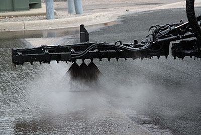Machine spraying hot liquid on road
