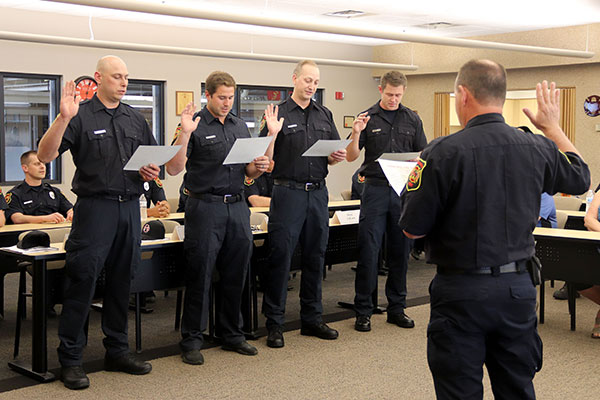 Four firefighters stand with hand in air reading oath of office