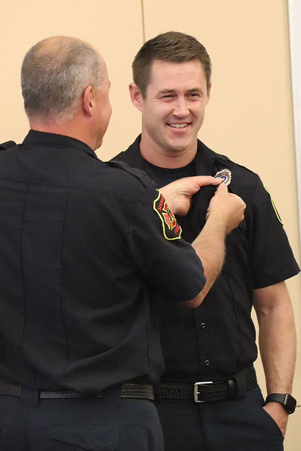 Firefighter pins badge on shirt