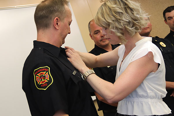 Woman pins badge on firefighter's shirt