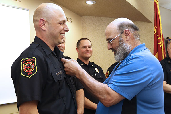 Father pins fire badge on son's uniform