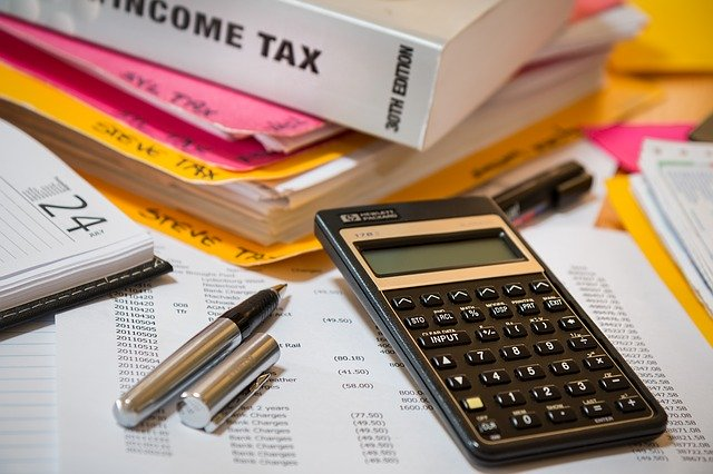 calculator and pen and income tax binder