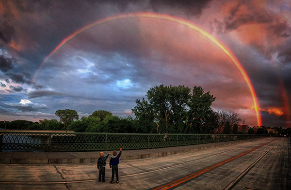 Two kids standing on bridge trying to reach rainbow