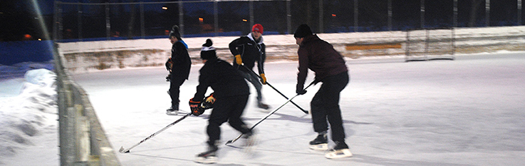 Skaters playing hockey at night