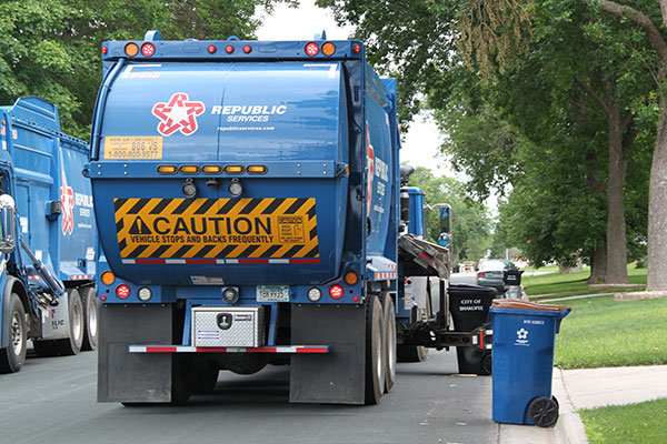 Garbage truck picking up can
