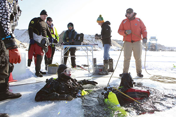 Divers in a frozen lake with people standing around