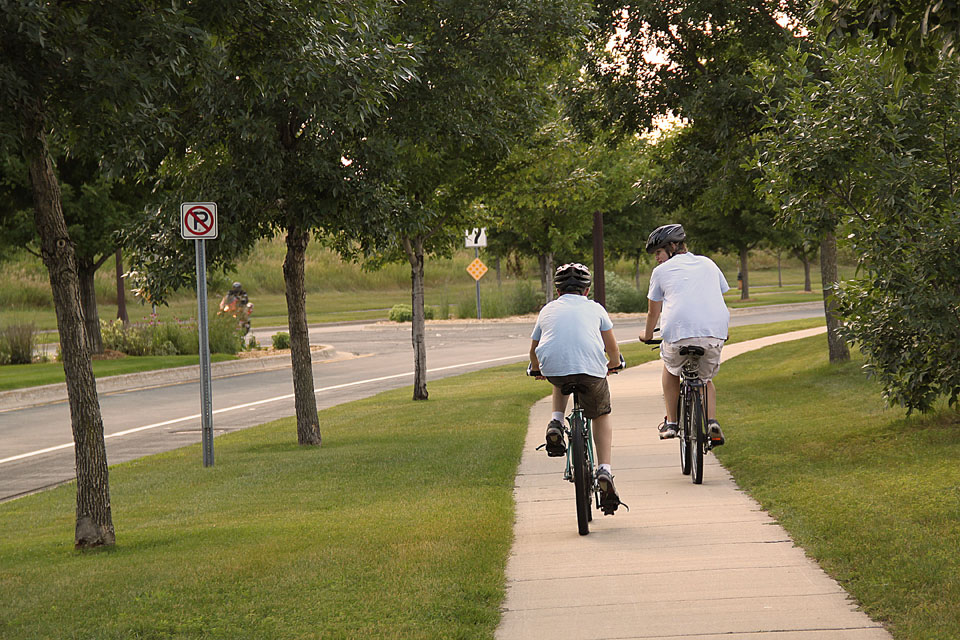 Two kids biking on sidewalk